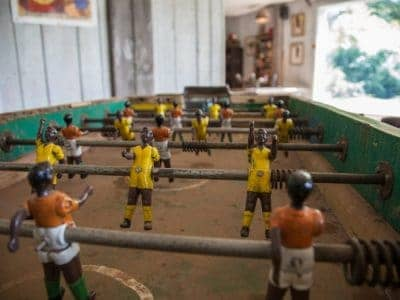 a real life foosball table showing the characters, the field you play on, the rods that players move to interact.